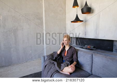Pretty attractive woman takes phone by hand and spends it on touch screen to answer husband's incoming call, chatting and laughing happily, sitting on gray soft sofa in lotus pose wrapped in plaid in stylish living room with gray walls