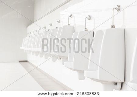 Closeup white urinals in men's bathroom design of white ceramic urinals for men