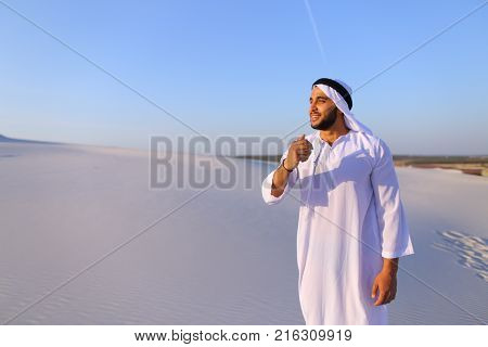 Young Arab guy who takes sand in hand and lifts it to smiling face and blows through fingers fine white grains of sand in bottomless desert on hot summer day. Swarthy, handsome Muslim with short dark hair dressed in kandura, long