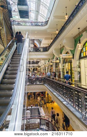 SYDNEY AUSTRALIA - NOVEMBER 24 2017; Inside destination retail center trendy and classy Queen Victoria Building retail arcade with peoplein cafe on different levels and riding escalator up.
