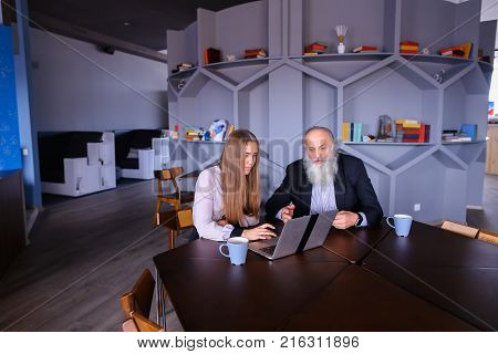 Elderly businessman see at laptop screen. Confident in himself gray old man makes deal with young woman in modern company office and sits at table with cup of coffee in fall. Beautiful stately gray head with long beard dressed in black classic suit and sh