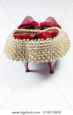 Woman's vintage faux pearl collar draped over vintage ruby red shoes rear view copy space vertical aspect