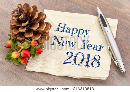 Happy New Year 2018 - handwriting on a napkin with a pine cone