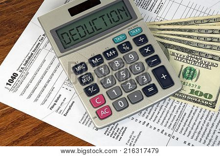 deduction text on silver calculator with American hundred dollar bills on 1040 income tax form
