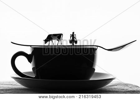 miniature farmer's wife with a cow on a Cup of coffee