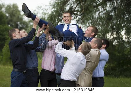 Belarus, the city of Gomel.July 15, 2017.Central Wedding House.Merry groom. Grooms are friends. Throw the groom up.