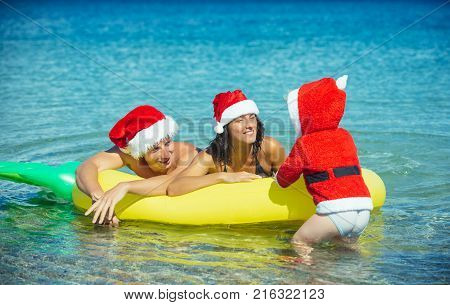 New year man girl with small boy. Xmas party celebration fathers and mothers day. Santa child parents at Christmas. Winter holiday vacation. Christmas happy family on pineapple mattress in water.