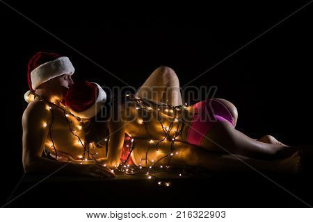 Santa man and girl with naked body. Christmas couple in love of sexy man and woman. Relations of couple in illuminated garland. Love and sex games. New year boyfriend and girlfriend isolated on black.