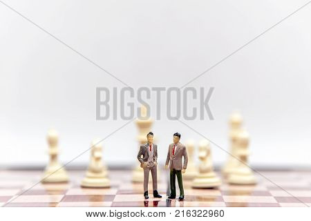 Miniature businessman and partner lawyers or politicians on a chessboard. Business Concept