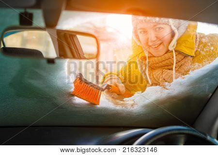 Caucasian woman scraping and cleans snow off car windshield