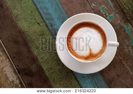 Top view of hot coffee with heart shaped latte art in white cup served on colored rustic style wooden table