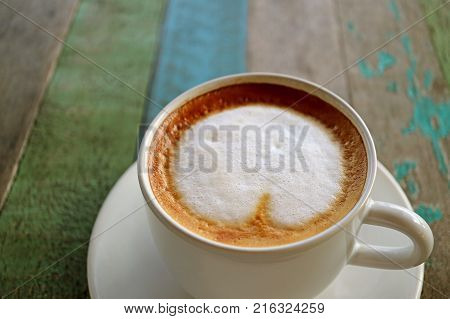 Closed up a cup of hot coffee with milk foam served on colored rustic style wooden table