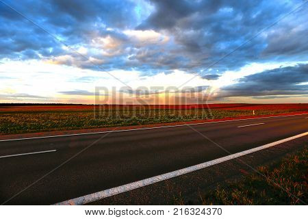 Outgoing road at sunset.Landscape from the outgoing road fields and sky