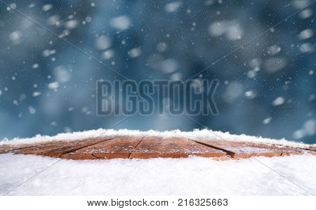 Wooden Table, Bench Covered In Snow With A Christmass, Wintery And Snowy Background With Space To Ad