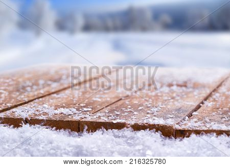 Wooden table top covered in snow with a Christmass winter and snowy background with space to add products and text.