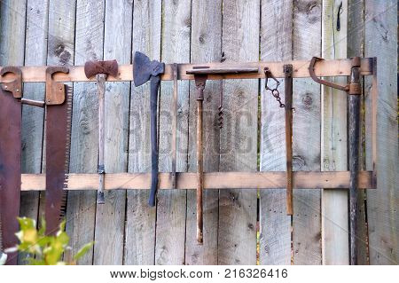 various tools hanging on wooden old fence