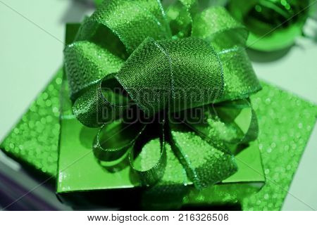 Square shaped shiny green gift box with gritter green ribbon bow, closed up with selective focus