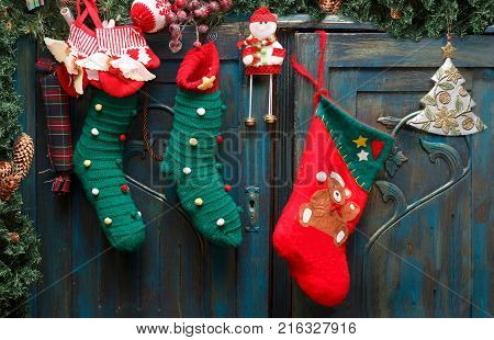 Christmas decorations: red boot green stockings evergreen branch with pine cones and christmas toys on blue doors of old wardrobe.