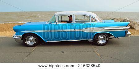 FELIXSTOWE, SUFFOLK, ENGLAND - AUGUST 27, 2016: Classic Blue Pontiac Star Chief Motor Car  parked on seafront promenade.