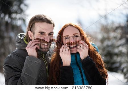 Young couple making fake mustache from hair