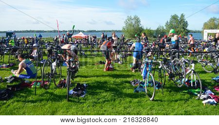 GRAFHAM, CAMBRIDGESHIRE, ENGLAND - MAY 21, 2017:  Triathletes at end of  swimming  stage in change over area with bicycles.