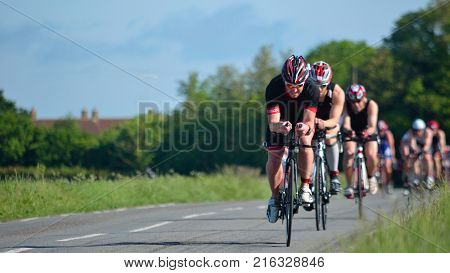 GRAFHAM, CAMBRIDGESHIRE, ENGLAND - MAY 22, 2016:  Triathletes on road cycling stage of triathlon.