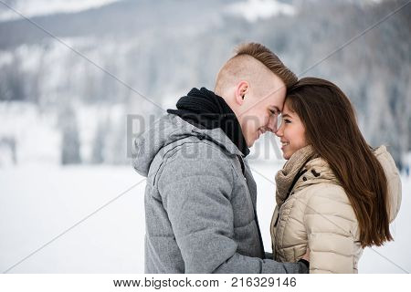 Cheerful teen couple in love touching foreheads