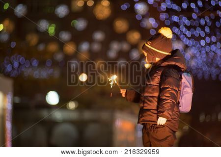 Little boy with sparkler on blurred bokeh background Outdoors photography. Boy is looking at sparkler in his hand.