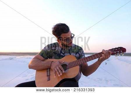 Ambitious budding musician, Muslim guy performs lyrical melody on musical instrument and guitar, and raises skill of professionalism, sitting on sandy hill in middle of wide sandy desert on warm summer evening at sunset. Swarthy man with dark hair