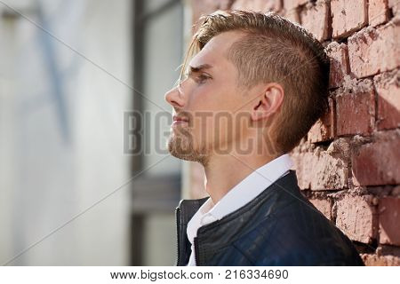 lifestyle and people concept - portrait of young man in leather jacket over brick wall outdoors