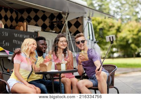 leisure, technology and people concept - happy young friends with food and drinks and taking selfie at food truck