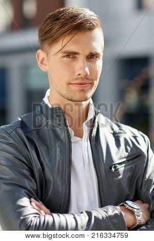 lifestyle and people concept - portrait of young man in leather jacket outdoors
