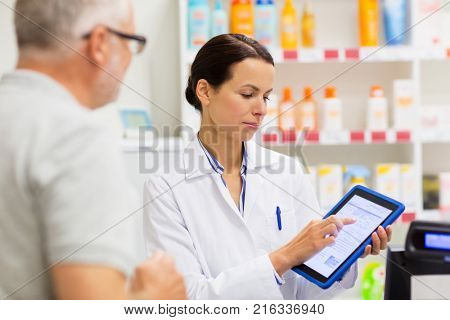 medicine, pharmaceutics, healthcare and technology concept - apothecary and senior customer with tablet pc computer at pharmacy