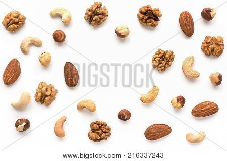 Isolated nuts pattern backdrop with copy space. Walnut, cashew, almond and hazelnut on white background. Top view.