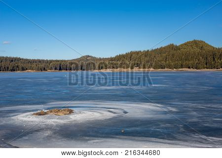 Winter landscape. Tiny figure of a fisherman on frozen lake waters, pine forest. Bulgaria, Rhodopes mountains, Shiroka Polyana lake. Sunny day with small white clouds. Rocky small island in front