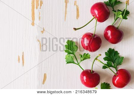 Fresh cherries on white rustic wood table in top view flat lay with copy space. Red cherry on wood background suitable for web cover or banner. Cherry have high vitamin C and have sweet and sour taste. Fruit background concept of cherry.
