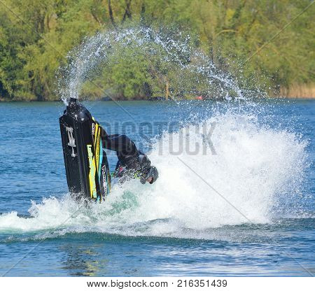 WYBOSTON, BEDFORDSHIRE, ENGLAND -  APRIL 09, 2017: Freestyle Jet Skier  competitor  performing back flip creating at lot of spray.