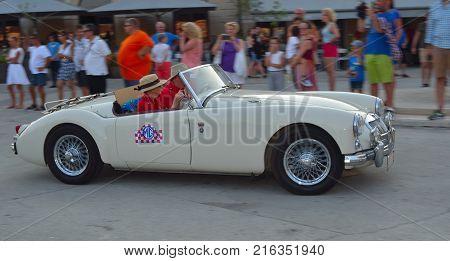 ROVINJ, ISTRIA, CROATIA - JUNE 25, 2017: Classic White MGA  being driven through town square in Rovinj in tour of Croatia.
