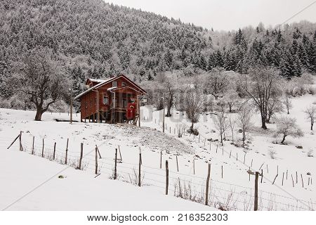 flagged wooden house in white winter black winter