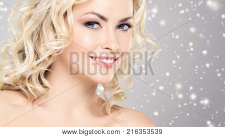 Beautiful face over Christmas background. Winter portrait of pretty blond woman.