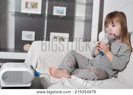 Little girl making inhalation with nebulizer at home. child asthma inhaler inhalation nebulizer steam sick cough concept Horizontal