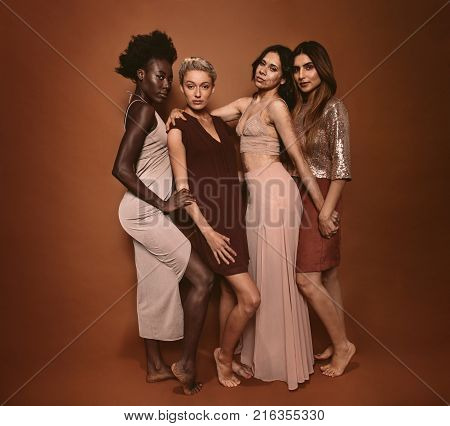Group of diverse women standing together against brown background. Multi ethnic females looking at camera in studio.