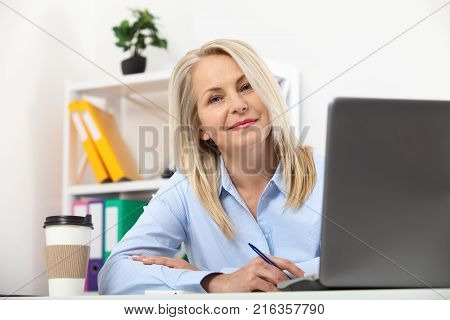 Business woman working in office with documents. Beautiful middle aged woman looking at camera with smile while siting in office.
