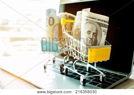 American dollars JPY money in trolley on laptop keyboard. Idea of exchange money online shopping Online shopping is form of e-commerce consumers to buy goods from directly seller through internet.