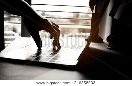 hands of anonymous hackers typing code on keyboard of laptop for remotely reach and receiving personal information online networking Internet Crime Payment Security Concept Silhouette black white