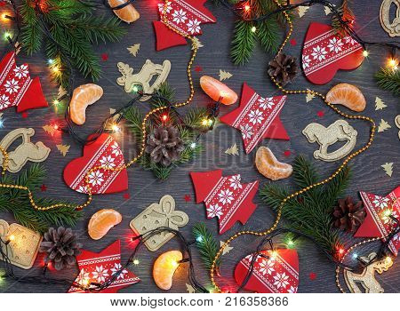 Christmas background with fir branches segments of mandarins garland and Christmas decorations in the form of trees and stars hearts and gifts horse and deer. Postcard for the New year.