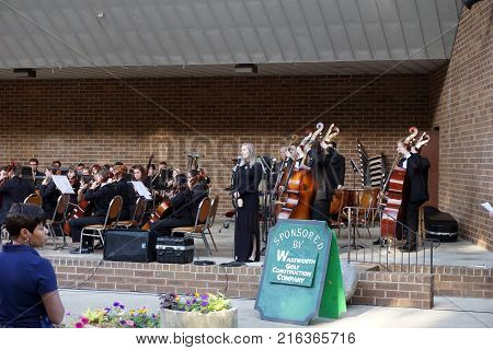 JOLIET, ILLINOIS / UNITED STATES - JUNE 1, 2017: A vocalist, accompanied by the Metropolitan Youth Symphony Orchestra (MYSO), sings the National Anthem at the beginning of a public concert at the outdoor theater in the Billie Limacher Bicentennial Park.