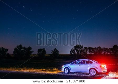 Dobrush, Belarus - August 12, 2017: Volkswagen Polo Vento sedan at night under the sky with the stars at the side of the highway. Sedan of the Volkswagen Polo in the night scenery under the starry sky on which is visible the Ursa Major