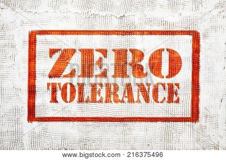 zero tolerance - red graffiti sign on a white stucco wall