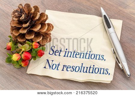 Set intentions. Not resolutions. New Year goals concept.  Handwriting on a napkin with a pine cone.